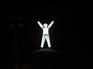 The Man raises his arms.